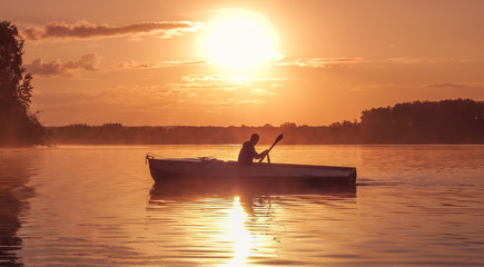 A young guy rides a boat on a lake during a golden sunset. Image of silhouette, Rower at sunset. Man rowing a boat in backlight of the sun. Unity with nature concept