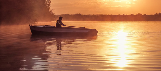 A young guy rides a boat on a lake during a golden sunset. Image of silhouette, Rower at sunset. Man rowing a boat in backlight of the sun