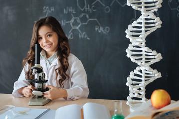 Cute little girl enjoying medicine experiment at school