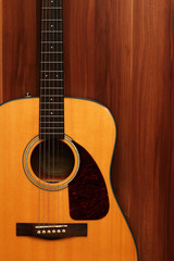 Acoustic guitar on a wooden background.