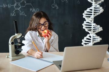 Amused little scientist enjoying homwework in the laboratory