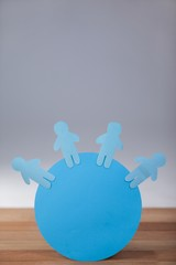 Blue paper cut-out people on the circle