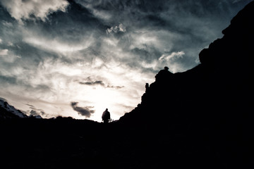 silhouette man with a backpack in camouflage rises to the top of the mountain