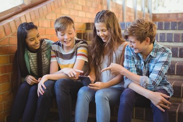 Smiling school students using mobile phone