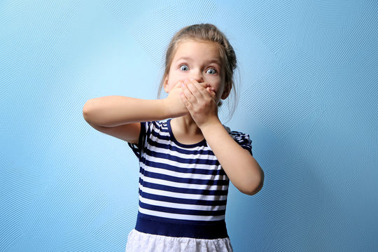 Cute little girl covering mouth with hands, on color background