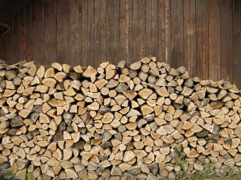 Pile de bûches en bois de mélèze devant une grange