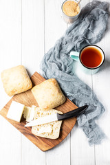 A cup of tea and ciabatta with butter on a white wooden background, soft selective focus, vertical, top view