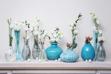 Beautiful composition with fresh flowers in vases on mantelpiece