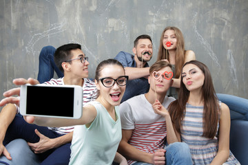 Happy young friends taking selfie while sitting on sofa near grunge wall