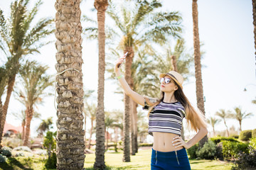 young woman taking selfie with smartphone on summer palms background. Summer vocation,