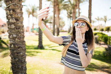 Woman take selfie on phone on palms and send kisses backgrounds. Summer vocation concept.