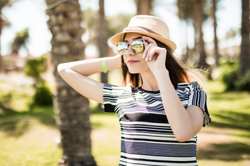 Cheerful young woman in hat and sunglasses in summer palms backgrounds. Summer vocation.