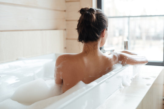 Young woman having bubble bath and looking at window