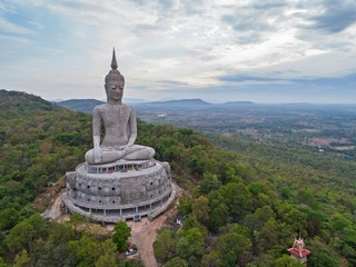 aerial view of Big Buddha sitting image on mountain with blue sky clouds at mukdahan province, Thailand.