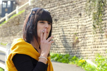 young brunette woman smoking  cigarette outside