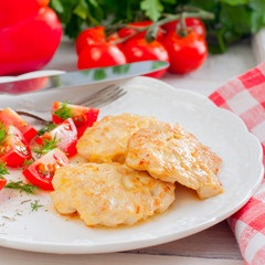 Chicken cutlets chopped with tomatoes on a white plate, selective focus,square