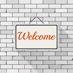 Simple white sign with text 'Welcome' hanging on a gray brick wall. Grunge brickwork background, textured rough surface. Creative business interior template for shop, store, supermarket.