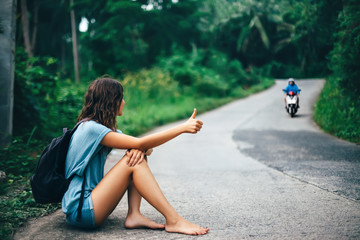 Young beautiful woman hitchhiking sitting on road