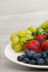 Fresh fruits on a wooden background. Strawberries, grapes, blueberry closeup