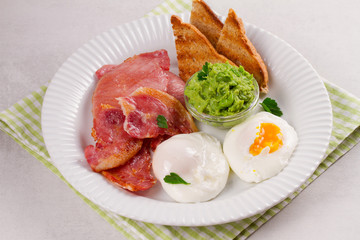 Bacon, poached eggs, mashed peas and toasts on white plate. Grilled rashers and eggs