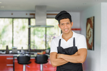 Private Thai chef in a modern style home kitchen. Waist portrait, arms crossed over chest