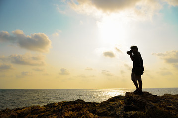 Silhouette of photographer taking photo on the top of mountaing