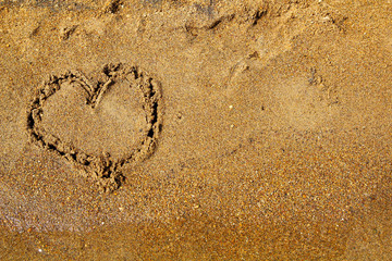 Picture of a heart drawn in the sand of the beach