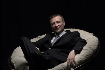 Mature businessman sitting in chair on black background