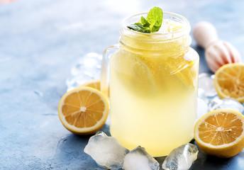Fresh lemonade in mug jar with ice and mint Fresh lemon and squeezer Copy space Horizontal photo