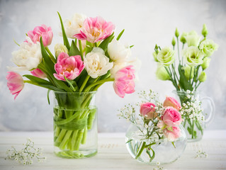 Beautiful flowers bouquet in vase on the wooden table.Tulips,roses and eustoma.