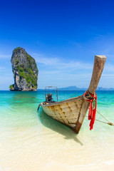 Thailand summer travel sea, Thai old wood boat at sea beach Krabi Phi Phi Island Phuket park on white sand blue sky emerald green ocean water.
