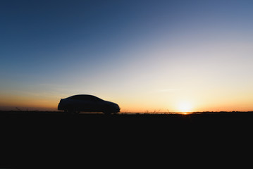 Car silhouettes against  sunset