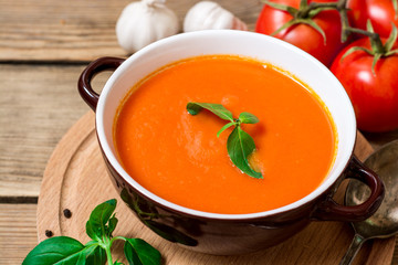 Tomato soup in ceramic bowl on wooden background.