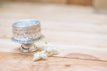 Thailand Songkran festival decoration concept, water in silver bowl with jasmine white flower.