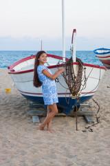 Girl near boat in the beach