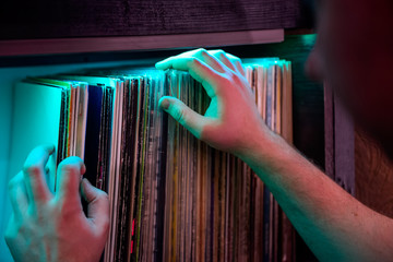 Close up man's hands browsing through vinyl records collection. Music background. Selective focus