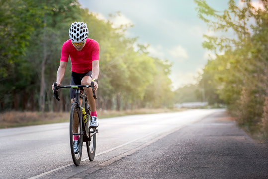 Asian men are cycling road bike on asphalt road during sunset time