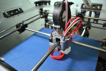 Work 3d printer close. Printing 3D printer Object Orange plastic On blue background. Plastic Wire Filament, Modern printing technology. Progressive additive technology