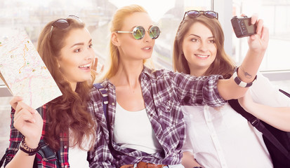 three young girls in sunglasses doing selfie on the computer tablet