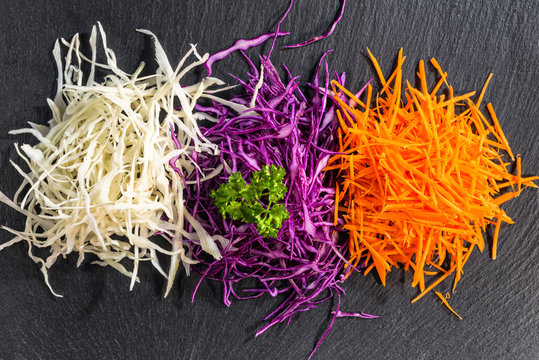 flat lay of mix finely chopped white, red cabbage, carrot decorated parsley on black slate stone background, concept healthy eating