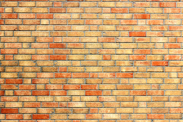 Yellow brick wall with red bricks