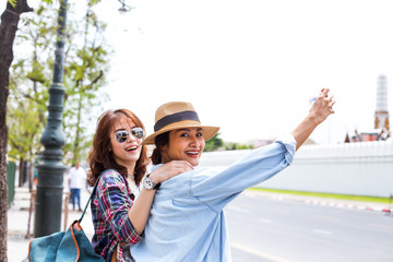 Two girlfriends taking photos while traveling to Grand- Palace in Bangkok,Thailand