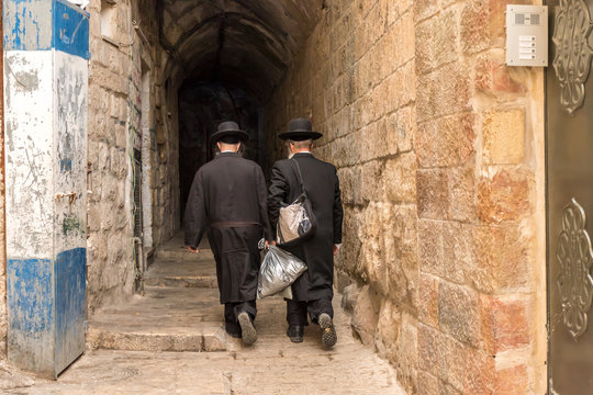 A narrow street in East Jerusalem with a couple of religious Jews.
