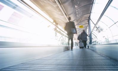 futuristic airport walkway with blurred passengers