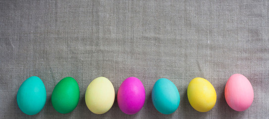 Pattern of Rows of colored easter eggs grey linen textured background. Easter web Background.