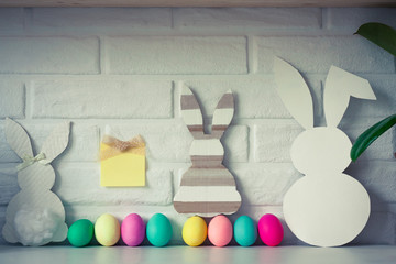 Easter white bunny with colored eggs with sticky note against white brick wall background. Cute Easter celebration decoration. Copy space for text. Happy Easter card. Easter concept.
