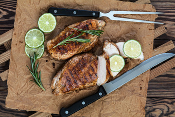 Sliced grilled chicken filet with herbs  on a paper on wooden background. Rosemary and sliced lime on a dark groundwork.