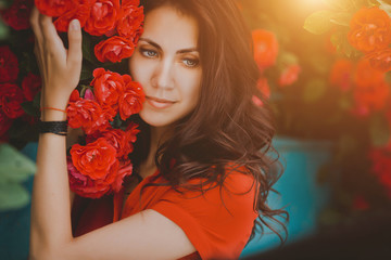 Beautiful portrait of sensual brunette woman close to red roses. Toned image