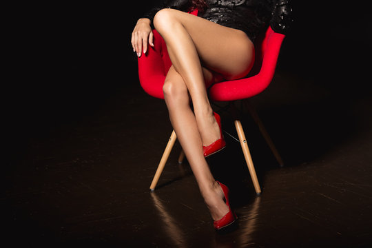 Perfect woman legs in high heels. Attractive, long legs of young woman wearing seductive lingerie posing in a sensual way in dark room by red modern chair
