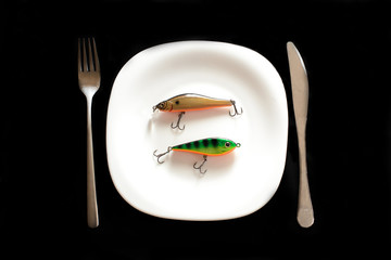 Delicious fried fish ( fishing bait) on a white plate with a black background